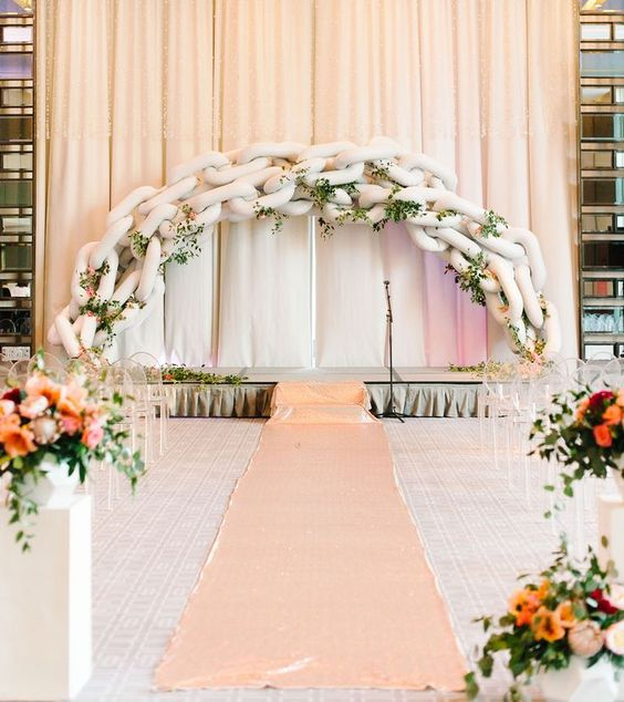 a unique chain balloon wedding arch with greenery and blush blooms interwoven for a fantastic look