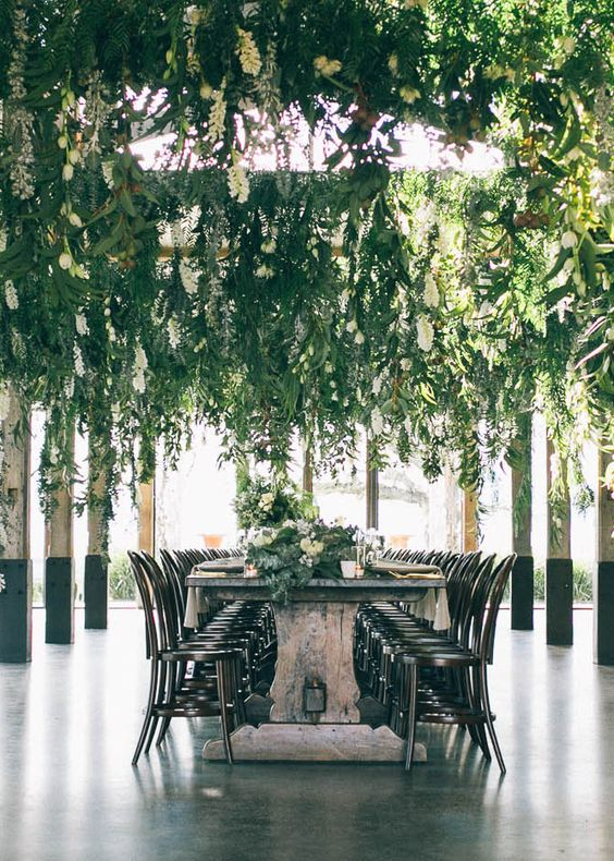 a wedding reception done with hanging greenery and neutral blooms plus matching table runners