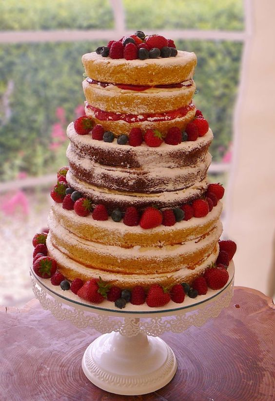 a coffee, chocolate and vanilla vegan gluten-free naked wedding cake with fresh raspberries, strawberries and blueberries