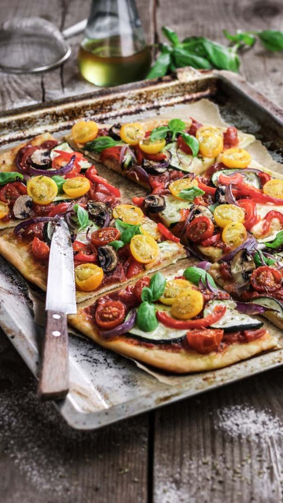 vegan pizza with various tomatoes, eggplants, peppers looks bright and bold