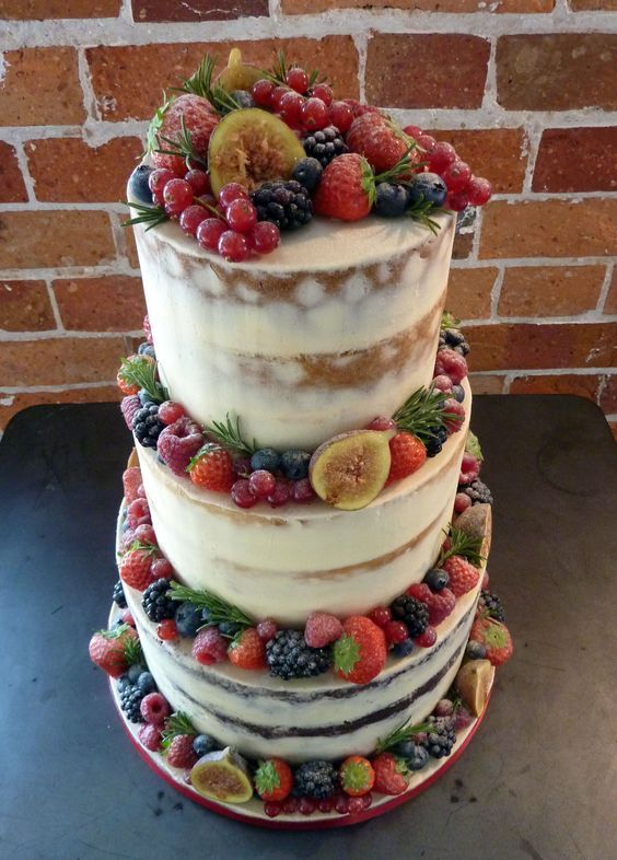 a delicious semi naked vegan wedding cake decorated with fresh fruit including figs, blackberries, blueberries,strawberries and others