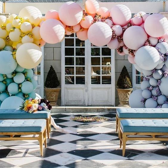 a pastel gradient balloon wedding arch in blue, yellow, peachy, pink and lilac plus blooms in between