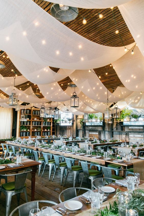 lots of airy neutral fabric hangings with lights is a cool maximalist idea for wedding decor