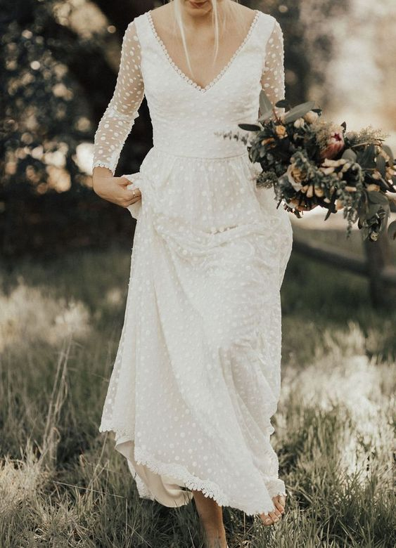 a romantic polka dot wedding dress with a V-neckline, long sleeves and a lace edge for a modern boho bride