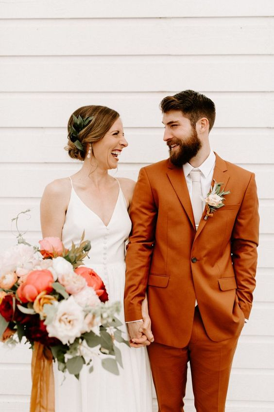 a rust colored groom's suit with a neutral tie and shirt is a chic and trendy idea of a colored look