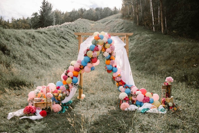 a rustic wedding arch with some tulle and colorful balloons and blooms looks unusual