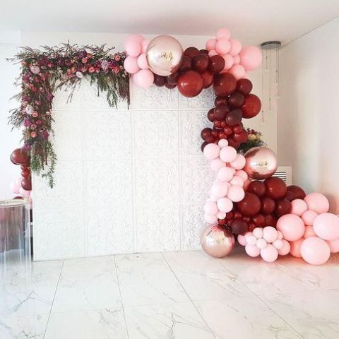 a beautiful wedding backdrop decorated with lush greenery and blooms on one side and burgundy, copper and pink balloons on the other