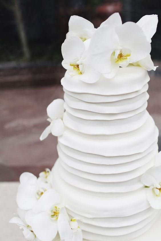 a white textural wedding cake topped with fresh white orchids is a catchy piece