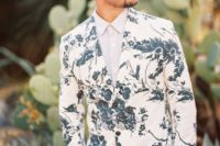 19 a modern and trendy groom's look with black pants, an off-white shirt and a white blazer with a botanical print