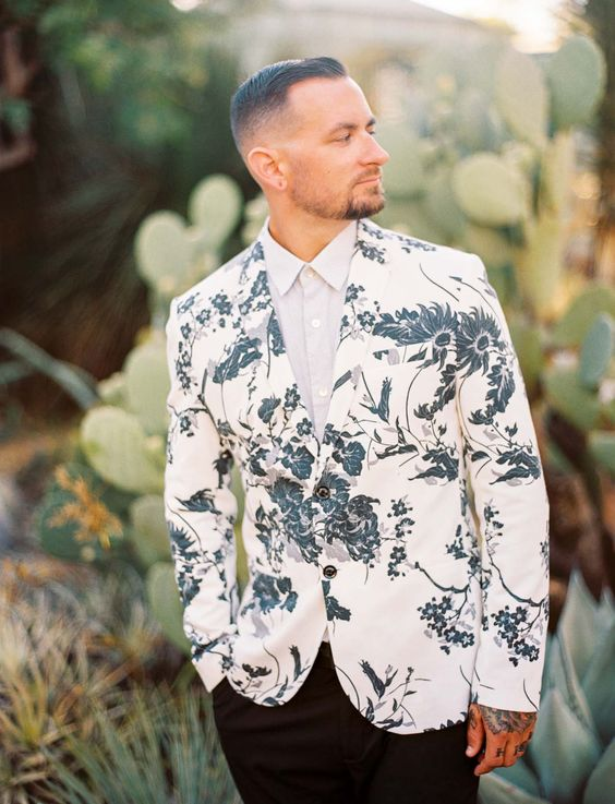 a modern and trendy groom's look with black pants, an off white shirt and a white blazer with a botanical print