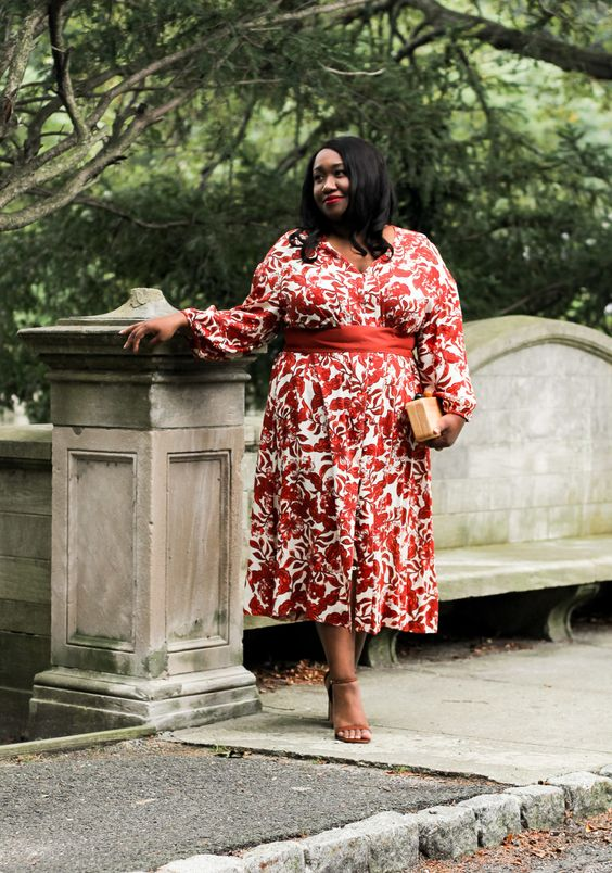 a red and white floral print midi gown with long sleeves, tan shoes and a small clutch