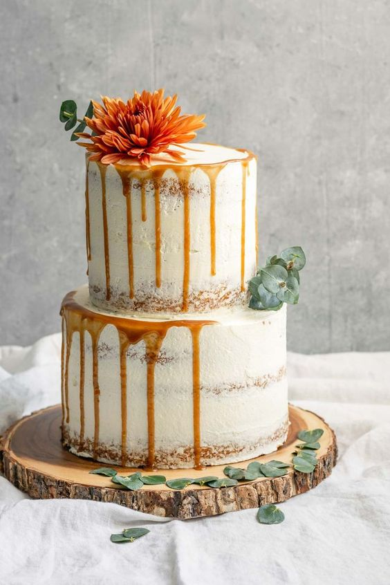 a semi-naked vegan vanilla wedding cake with dripping, greenery and a single bloom on top