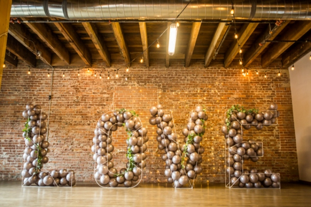 a creative wedding backdrop of wire letters filled with grey balloons and greenery interweaving for a modern wedding