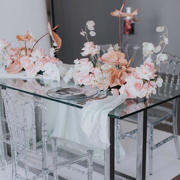 a modern wedding reception table of glass with pink roses, white orchids and coral anthurium floral decor