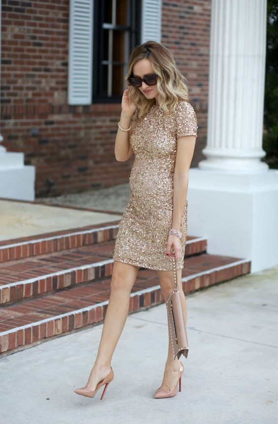 a sheath gold sequin over the knee dress with short sleeves, dusty pink heels and a neutral clutch