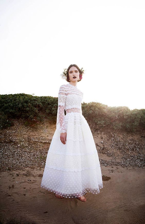 a unique midi A-line polka dot wedding dress with with sheer parts, lace, long sleeves and a high neckline