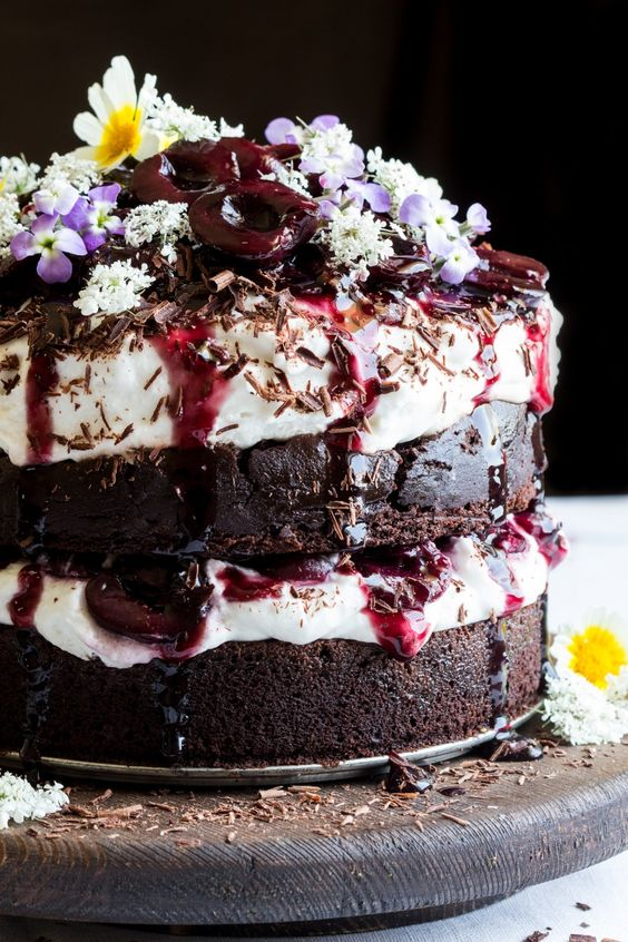 a vegan black forest cake with fluffy cream, drunken cherries, and moist chocolate layers