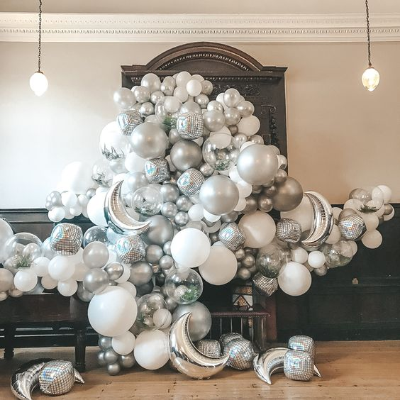 a dreamy white and silver balloon wedding backdrop of disco balls, moons and usual balloons