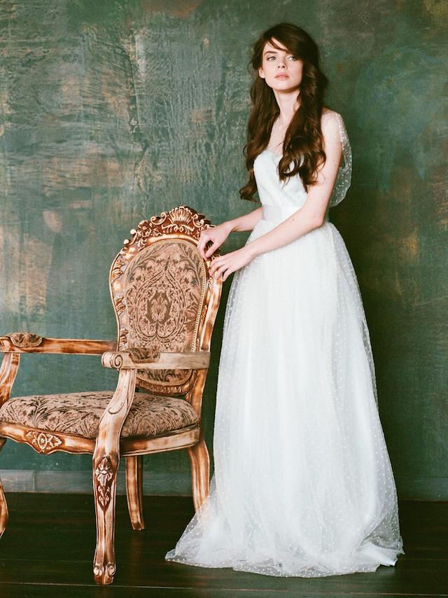 a very light blue polka dot A-line wedding dress with a silk sash and a small train
