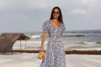 22 a gorgeous navy and white floral maxi gown with a deep neckline and short sleeves plus a small wicker bag