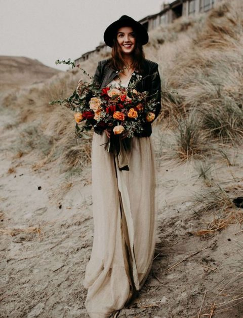 a neutral wedding gown accessorized with a black leather jacket and a black hat for a highlight