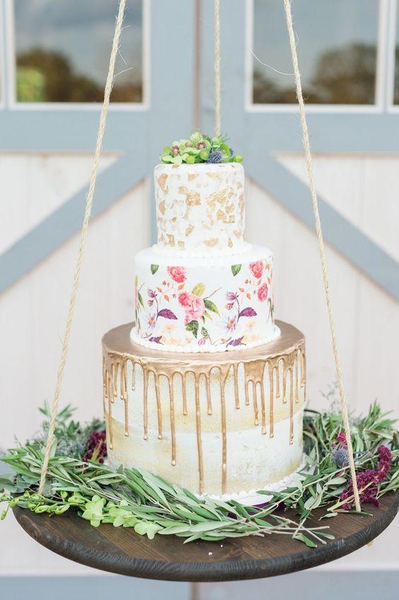 a trendy wedding cake combining metallic drip, handpainting and metallic leaf plus fresh blooms on top