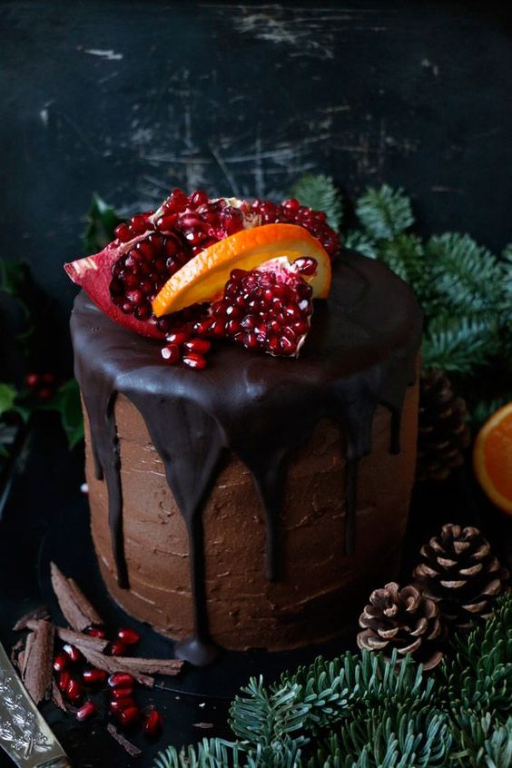 a vegan chocolate gluten-free and nut-free wedding cake with dripping, citrus and pomegranate on top