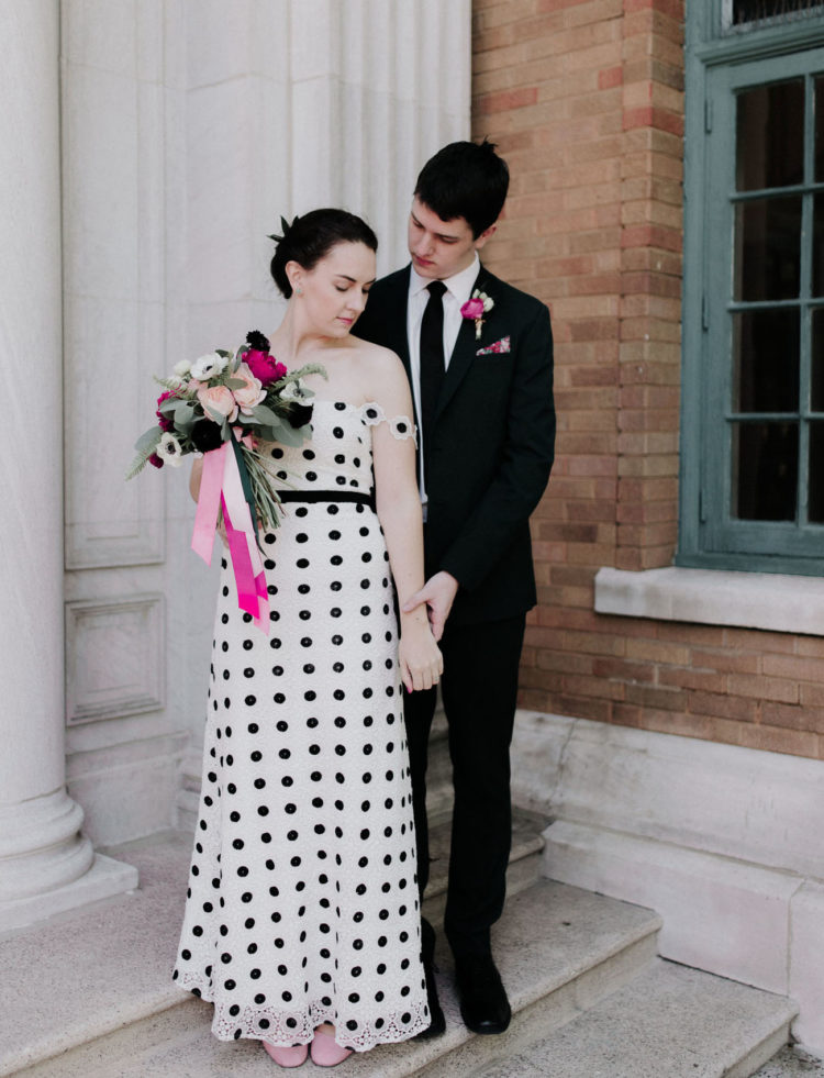 a very whimsy white and black A-line off the shoulder wedding gown with a lace trim plus pink shoes and statement earrings