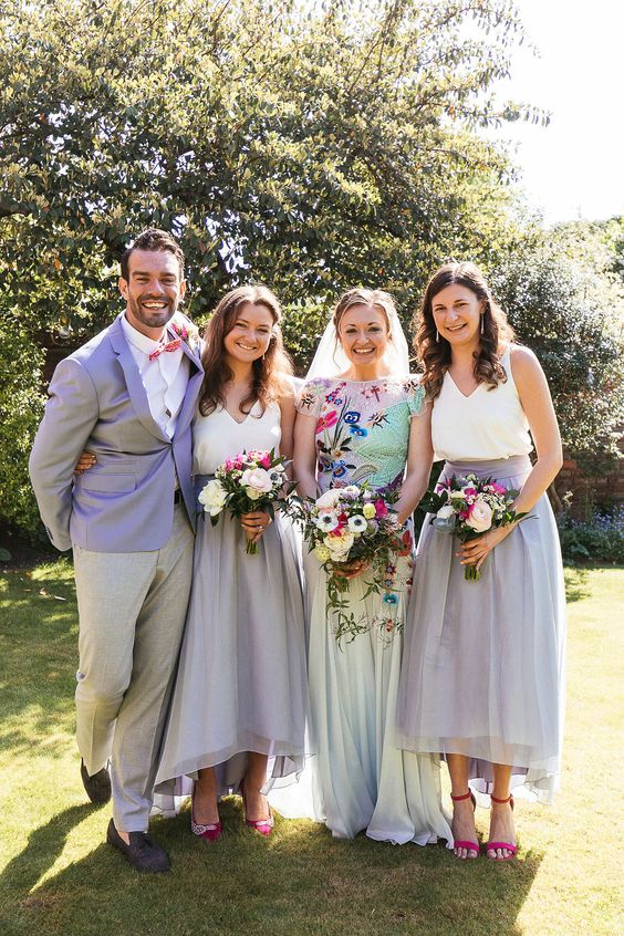 bridesmaids wearing lilac skirts and white tops, a bridesman wearing grey pants and a lilac blazer to match