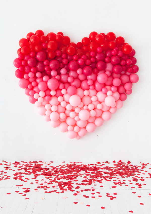 a giant ombre heart wedding backdrop and lots of pink and red hearts on the floor for maximal romance