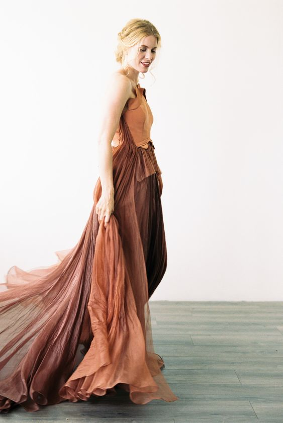 a gorgeous rust-colored wedding dress with a sculptural neckline and a layered skirt