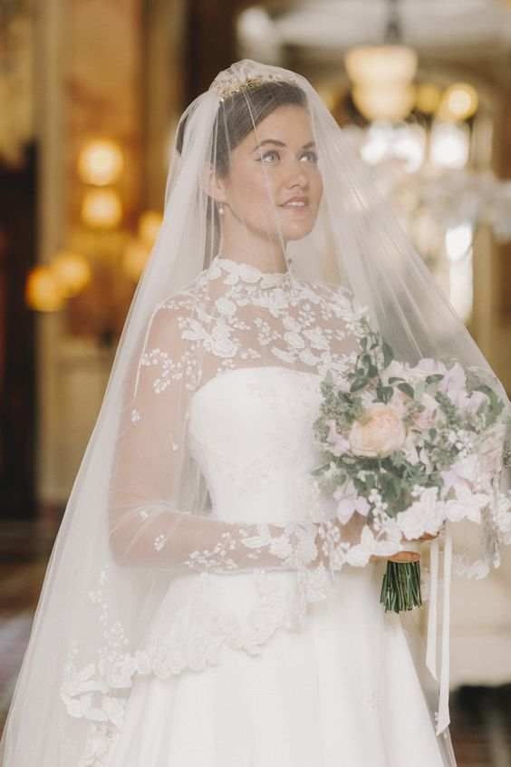 a romantic wedding ballgown with a high neckline, long sleeves and a matching veil