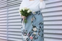 23 a tender spring wedding guest of a white top with long sleeves and a powder blue floral midi skirt, off-white shoes