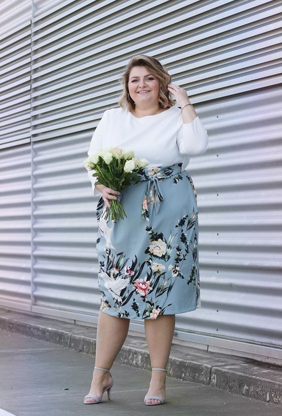 a tender spring wedding guest of a white top with long sleeves and a powder blue floral midi skirt, off-white shoes