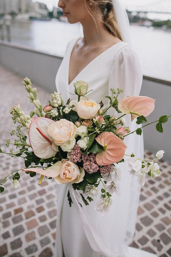 a tender wedding bouquet of pink anthuriums and blush roses plus lots of textural greenery