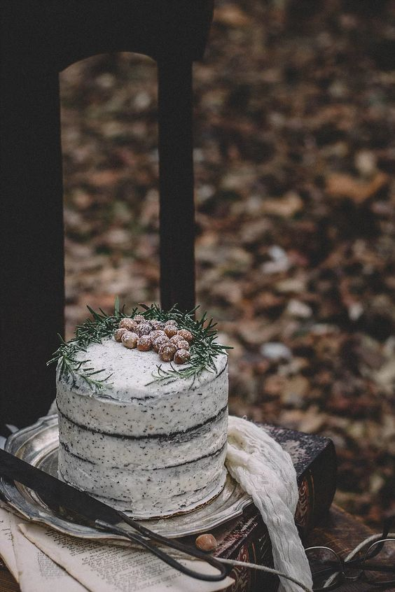 a vegan chocolate hazelnut wedding cake with London Fog buttercream and nuts and greenery on top