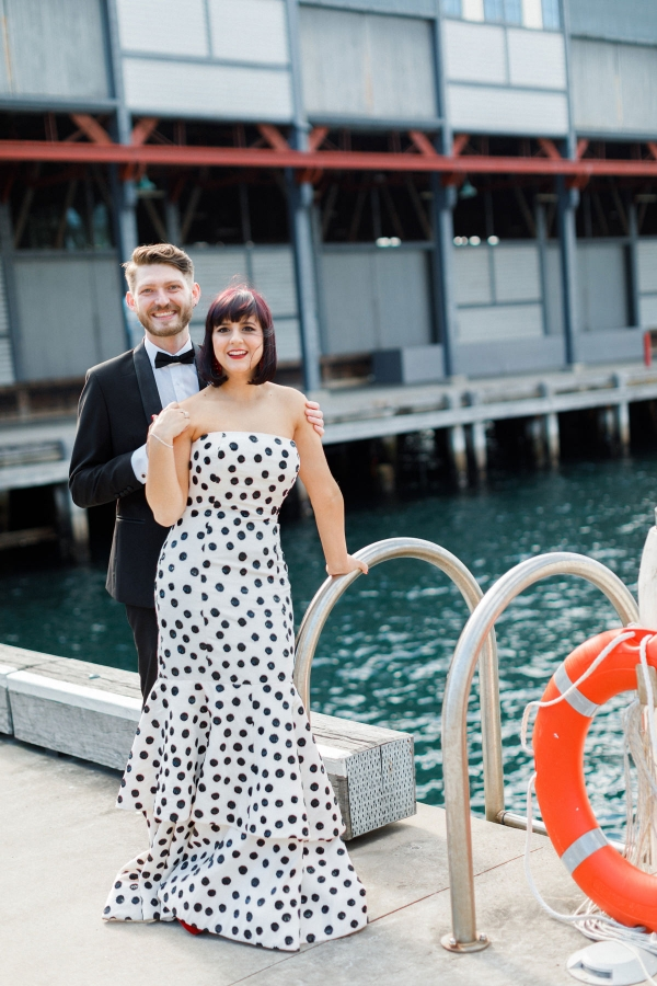 a whimsy black and white polka dot strapless wedding dress with a ruffled skirt paired with red shoes and a red lipstick