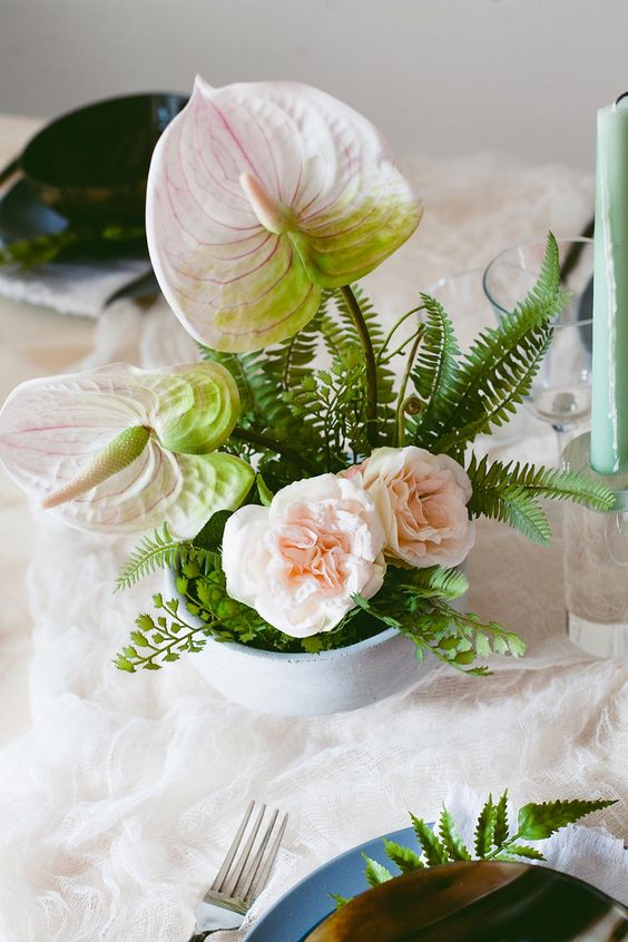 a beautiful summer wedding centerpiece with lots of greenery, blush anthuriums and peonies