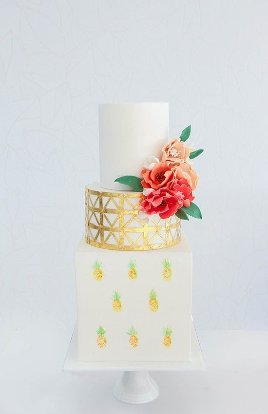 a creative wedding cake with handpainted pineapples, a metallic tier and a pure white one plus some sugar flowers