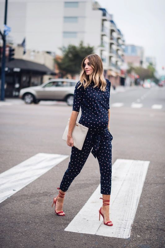 a navy printed jumpsuit with cropped pants, a white clutch and red lace up shoes for a more casual feel