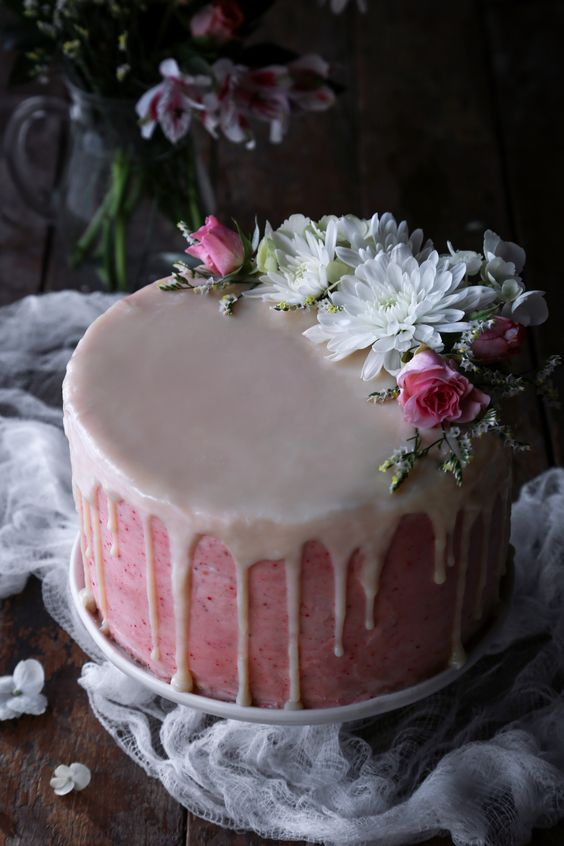 a vegan vanilla strawberry cake with dripping, white and pink blooms can be also done gluten-free