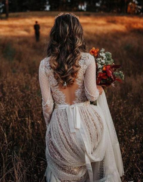 a whimsy polka dot wedding dress with long sleeves, a cutout lace back and a train looks very boho romantic-like
