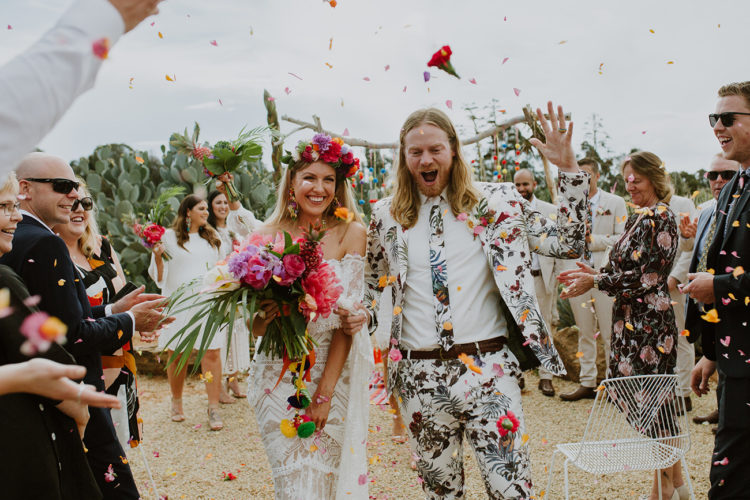 a white floral suit with a bright floral print and a matching tie plus a white shirt for a tropical wedding