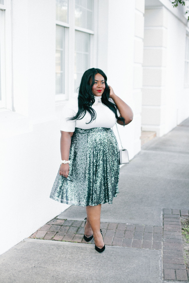 a white turleneck with short sleeves, a green high waist sequin midi, black shoes and an off-white bag