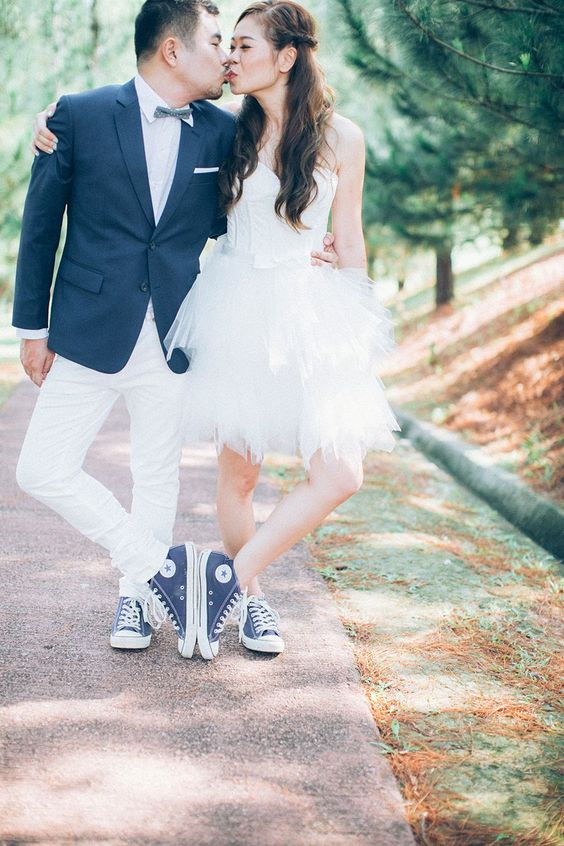 the bride and the groom wearing the same denim Converse sneakers for a matching look