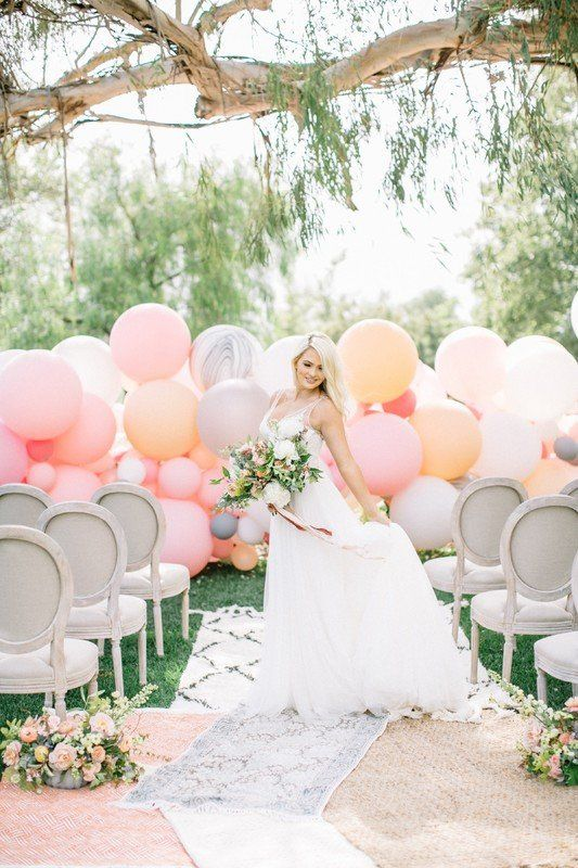 a soothing pastel balloon wedding backdrop in pink, peachy, soft orange and grey for a cool look