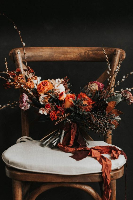 a textural and dramatic wedding bouquet with berries and rust blooms and ribbons for a fall wedding