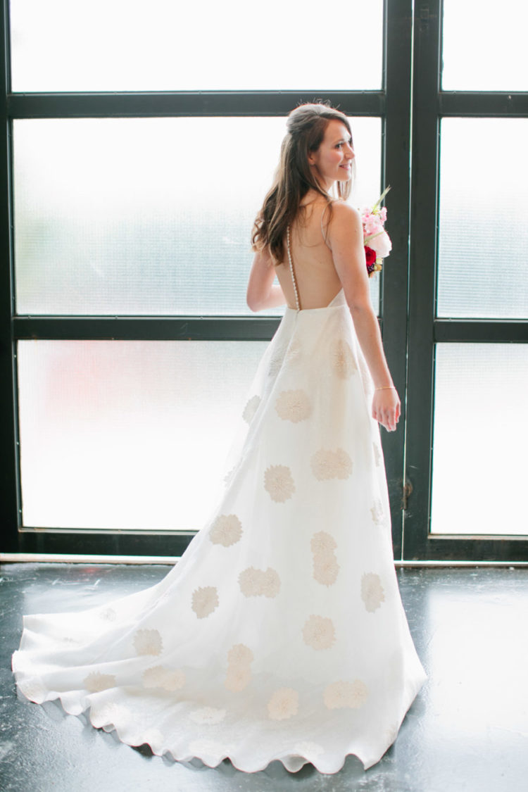 a white A-line wedding dress with tan polka dots, a train and a sheer back on a row of sparkling buttons for a modern bride