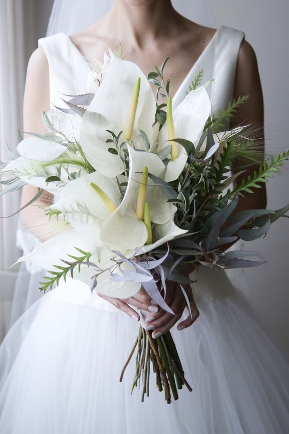 a beautiful wedding bouquet of various foliage and large white anthuriums