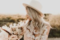 26 a chic boho lace wedding gown styled with a creamy fedora hat is a fantastic idea to rock